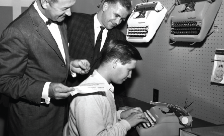 Three men around a typewriter