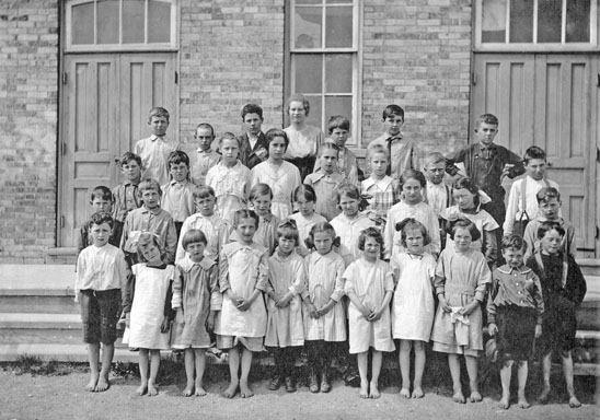 Children posing in front of school.