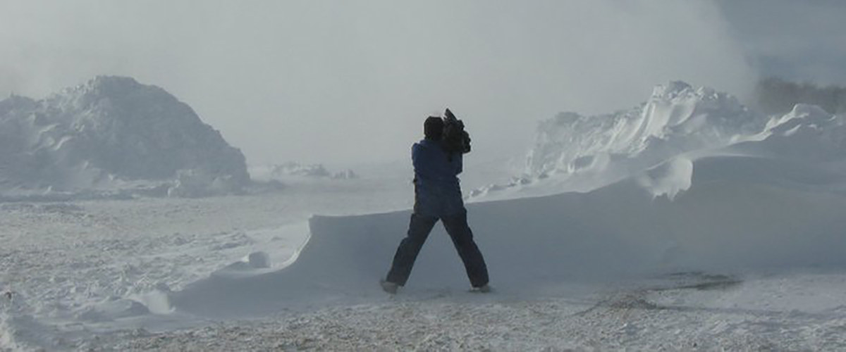 Man standing in the snow with a camera.