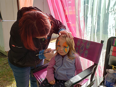 Adult applying face makeup to a child's face.