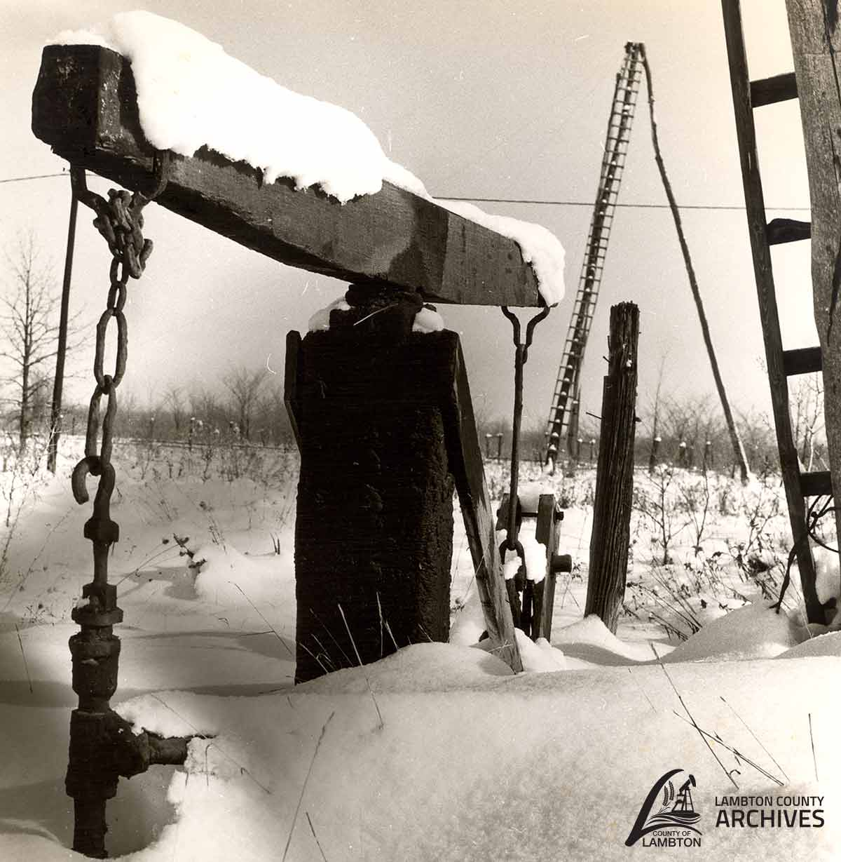 Black and white image of a jack pump in the snow.