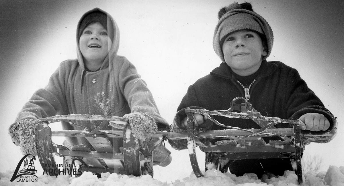 Black and white image of two children on a sled in the snow.