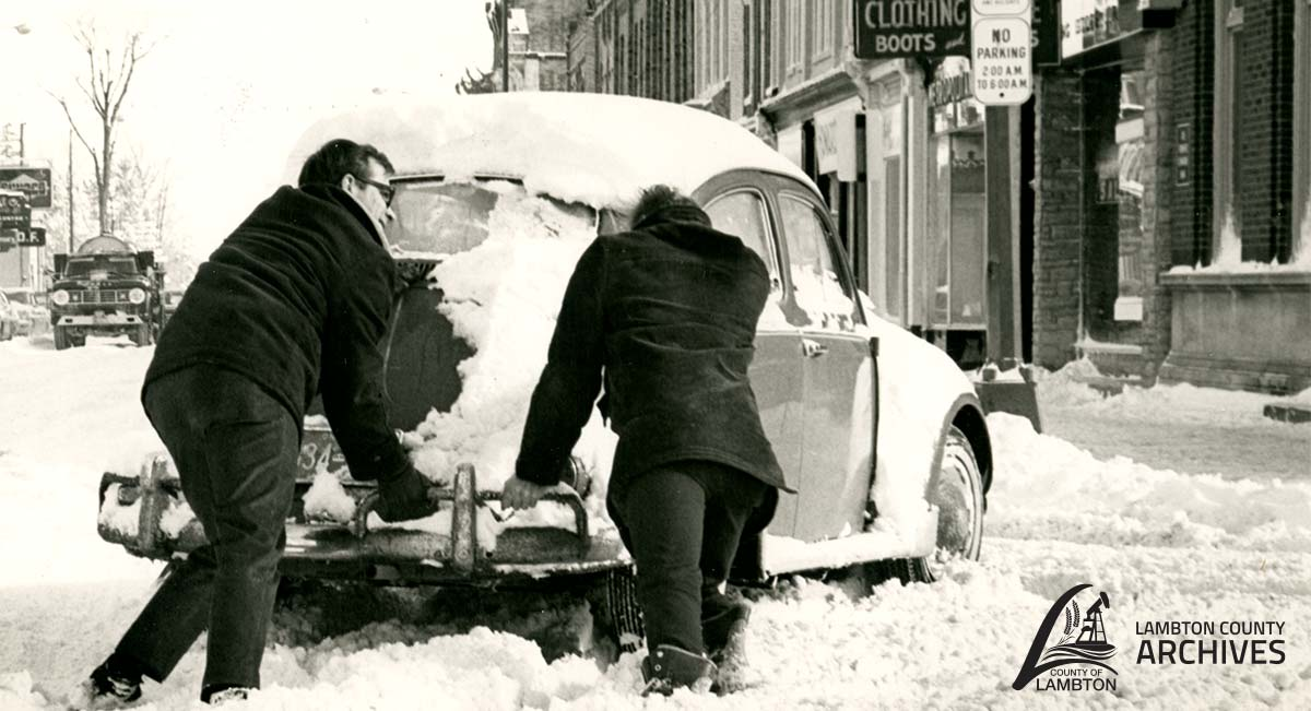 Image of two men pushing a car in the snow.