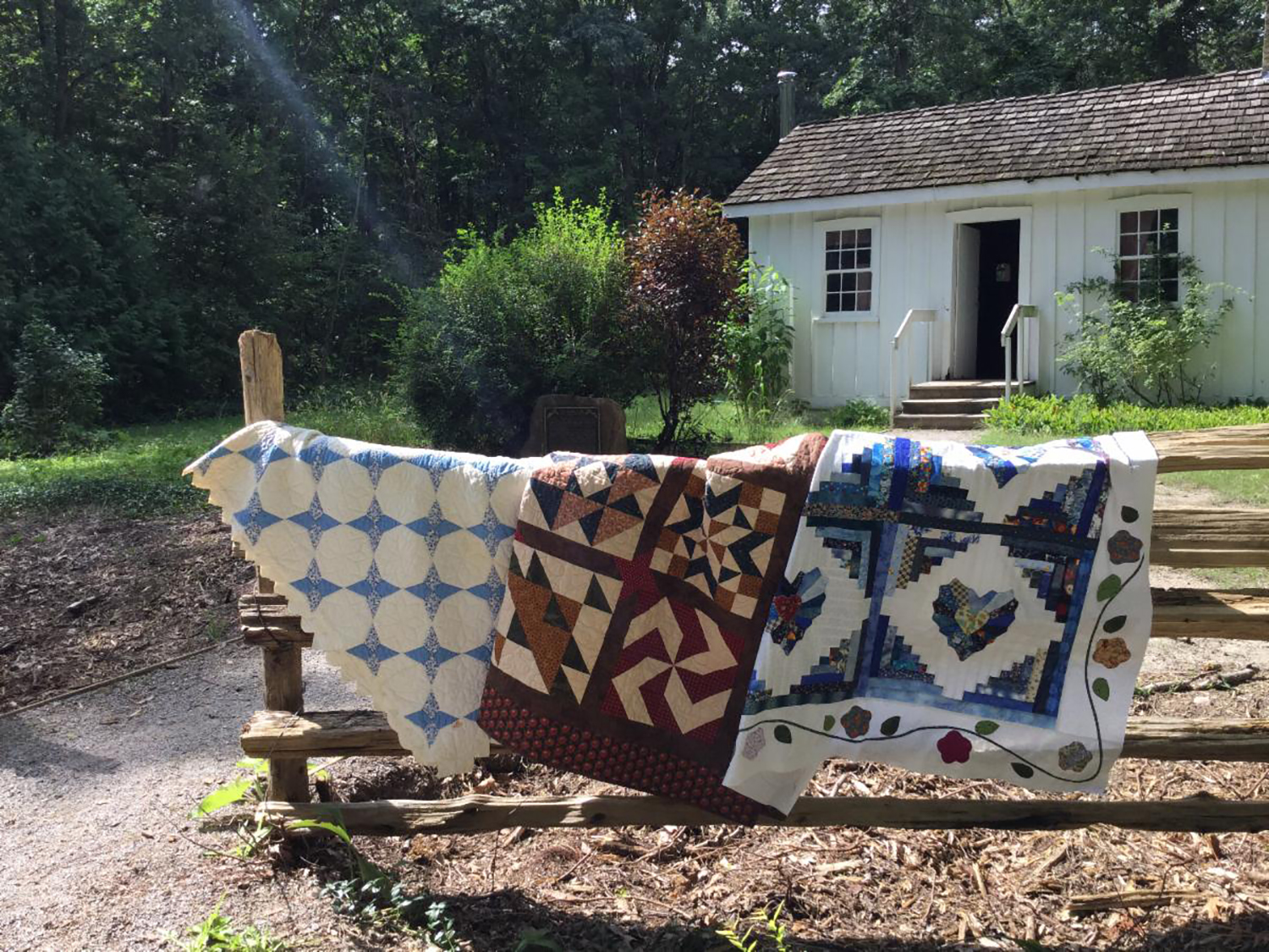 Quilts from the North Lambton Quilter's Guild hanging over fence in front of Tudhop house.