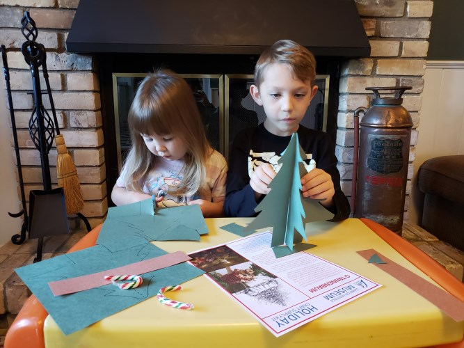 Two children sitting at a table cutting paper.