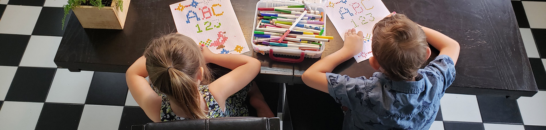 Two children sitting at a table with markers and paper.