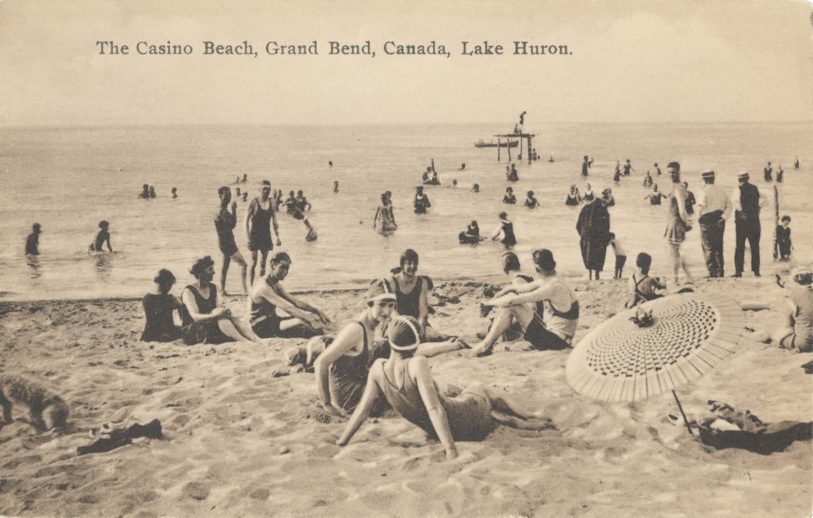 People sitting on the Grand Bend Beach.