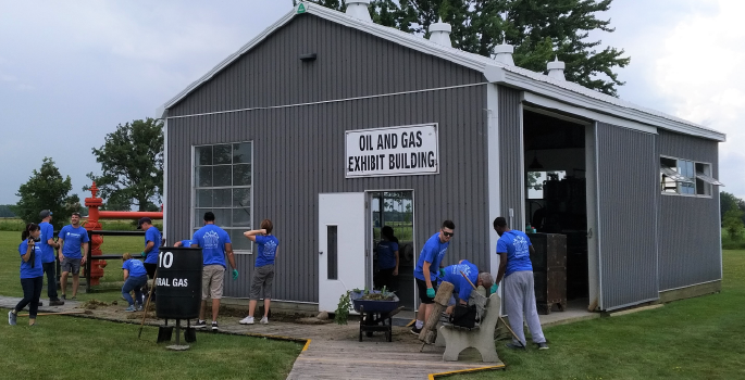 Volunteers outside the oil and gas exhibit building at OMC.