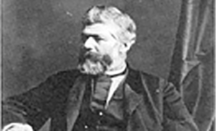 Black and white image of a man sitting.