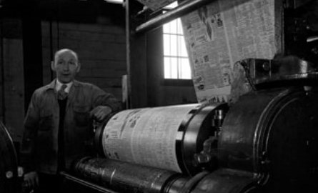 Man standing next to old press.