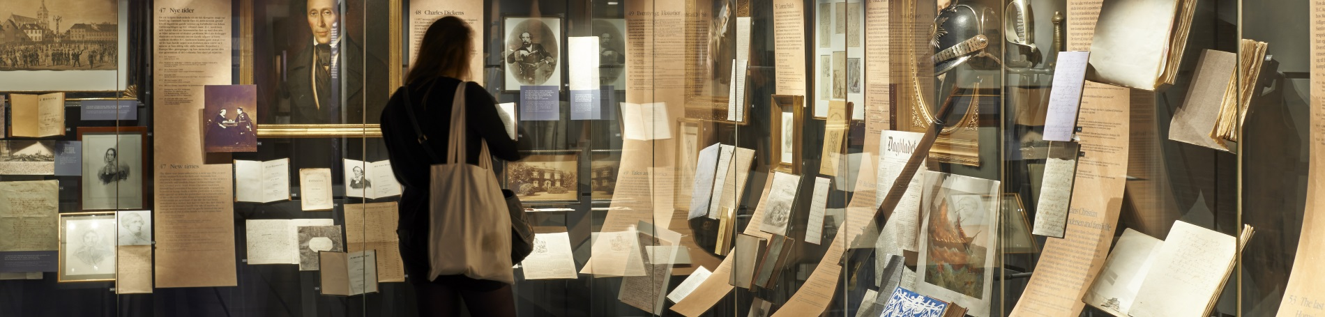 lady looking at a museum display of old artifacts